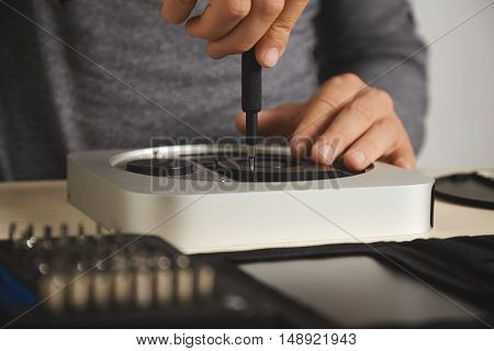 Close up shot of a man in a dark gray t-shirt using a small screwdriver on a computer