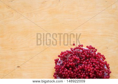 Red berries of viburnum on a plate on a woodden background.