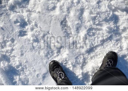 Adventure sport on snow background. Man dressed in black boots and snow pants. Top view