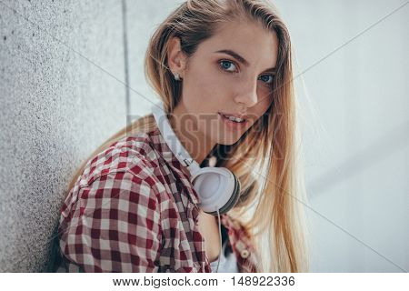 blonde woman standing near wall with headphones on the neck