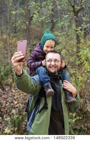Man taking a selfie with his daughter in an autumn forest. Soft focus on a man's face.