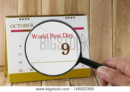 Magnifying glass in hand on calendar you can look World Post Day in 09 October concept of a public relations campaign.