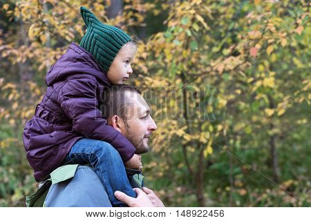 Father and daughter in an autumn forest. The girl is sitting on man's shoulders. They are looking forward. Shot with soft focus.
