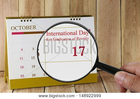 Magnifying glass in hand on calendar you can look International Day For Eradication of Poverty on 17 October concept of a public relations campaign economy and society.
