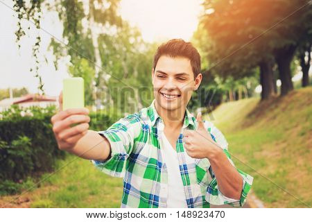 Young handsome brunet mixed race millennial man taking a selfie on smart phone, gesturing thumbs up, outdoors in autumn. Vibrant colors, natural light.