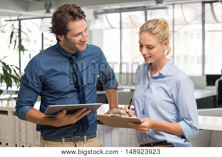 Smiling businessman and young businesswoman talking in office. Manager and employee working together. Happy business man with digital tablet working with his assistant.