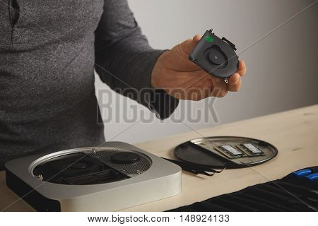 Close up of a man in gray t-shirt reparing a cooler on a computer