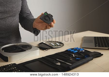 A man in a dark gray t-shirt looks at a cooler he took out of a computer, his tools in front of him on the table