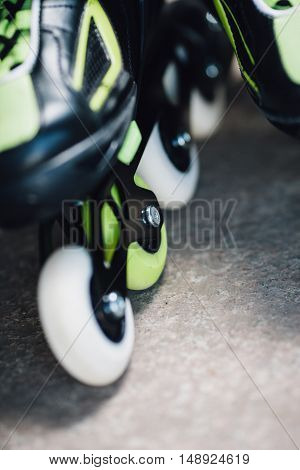 green and white wheels of roller skates closeup