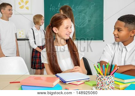 Schoolchildren sitting at table in classroom