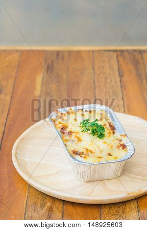 Homemade lasagne bolognese on wood table .