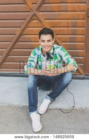 Cool millennial teenage guy with headphones and smart phone smiling, relaxing outdoors by the garage door, wearing casual street outfit, sitting and posing. Matte color filter applied.