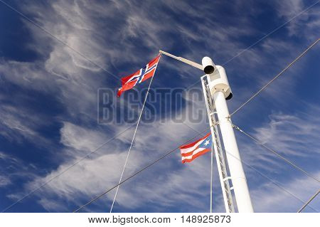 Norwegian flag waving on the wind on the mast against bright sky