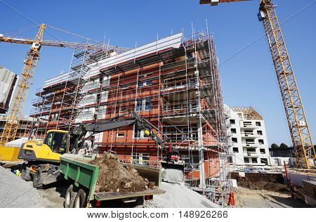 large construction site with cranes, bulldozers and scaffoldings