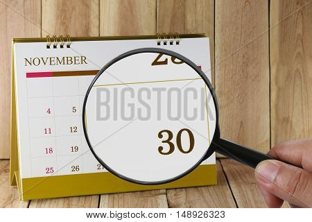 Magnifying glass in hand on calendar you can look Thirty days of monthFocus number thirty in NovemberConcept in business and meetings.