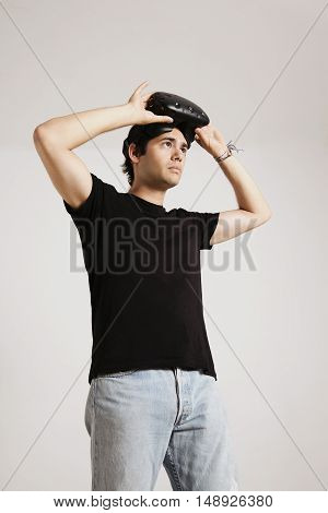 Young man in jeans and blank black cotton t-shirt putting on VR glasses against white wall background