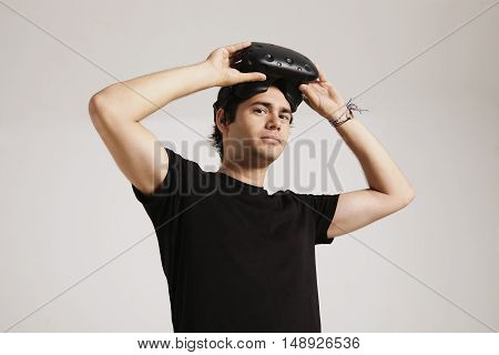A young man in unlabeled black t-shirt putting on VR headset looking into the camera isolated on white