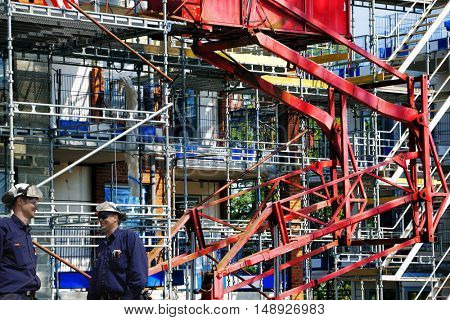 construction workers againt large building site, scaffolding and lifts