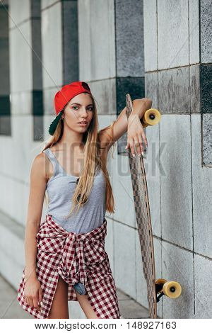 Portrait of beautiful girl in cap holding longboard and looking at camera