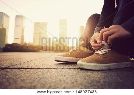 young skateboarder tying shoelace at sunrise city