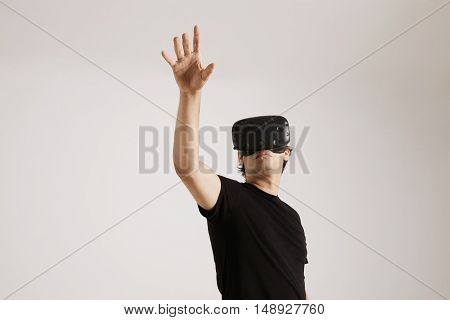 Young european model in blank basic cotton t-shirt and VR glasses touching someting isolated on white