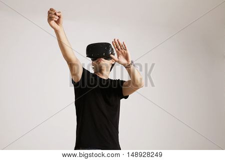 A young man in VR headset wearing plain black cotton t-shirt interacting with his environment isolated on white