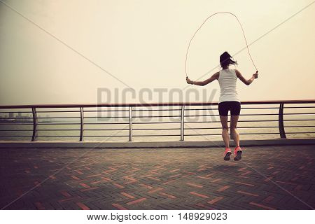 young fitness woman jumping rope on seaside