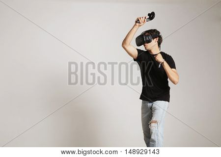 Young man in blank black t-shirt gaming golf or tennis in VR headset hitting someting isolated on white