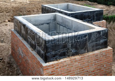 The construction process of node to connect water supply. Two rectangular concrete and brick boxes with waterproofing dug into the sand.
