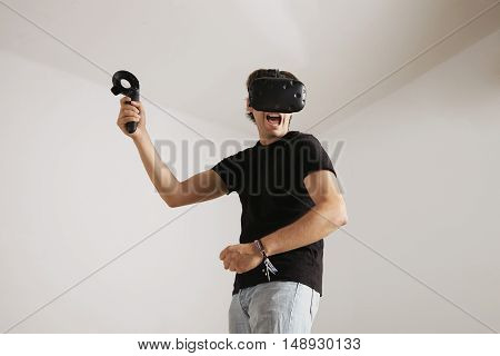 Low angle shot of a scary looking young gamer in jeans, blank black t-shirt and VR headset