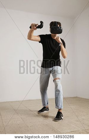 Full body shot of a young gamer in VR glasses and jeans and black unlabeled t-shirt playing a game in a room with white walls and light wooden floor.