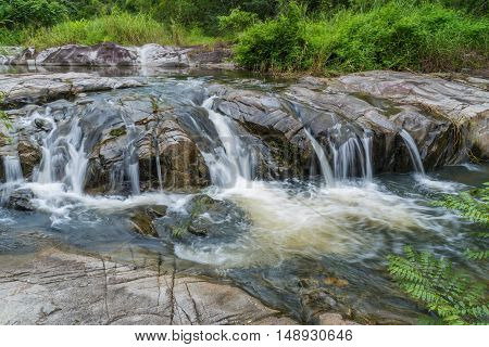 Waterfall flowing over flat rocks in forest.