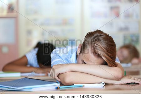 Tired schoolboy in classroom on lesson