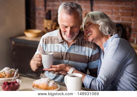 Togetherness. Smiling granny and grandpa holding white cups with tea and coffee during breakfast