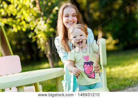 Happy mother with little daughter sitting on children's chair in park