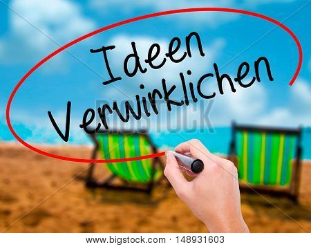 Man Hand Writing Ideen Verwirklichen ( Realize Ideas In German) With Black Marker On Visual Screen