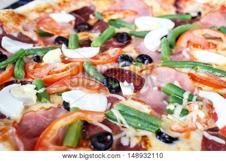 Close-up of Delicious Fresh Pizza with beans, cheese, ham and eggs