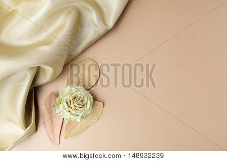 Satin on golden background with leaves. Flat lay. Owerhad view