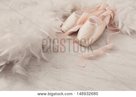 Pastel pink ballet shoes background. New pointe shoes with satin ribbon lay on white rustic shubby chic wood near feather boa, view with copy space