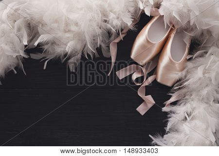 Pastel pink ballet shoes background. New pointe shoes with satin ribbon lay on black rustic shubby chic wood near feather boa, top view with copy space
