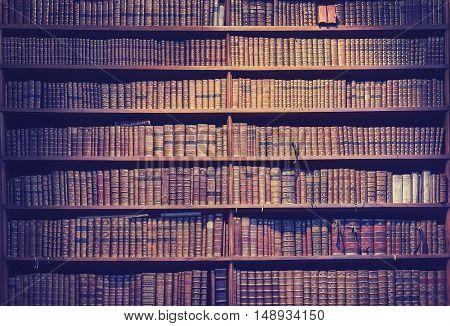 Vintage toned old books on wooden shelves wisdom concept background.