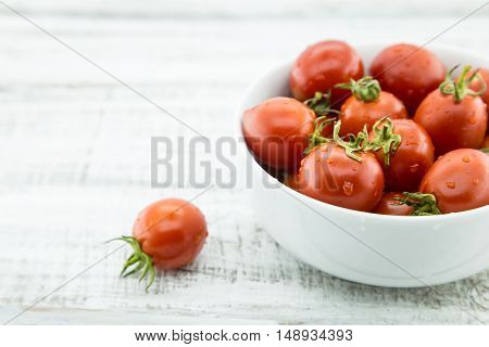 Fresh Cherry Tomatoes In White Ceramic Bowl On Rustic Wooden Background. Ingredients For Tomato Sauc