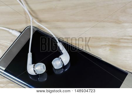 Headphone or earphone and smart phone on wooden background.