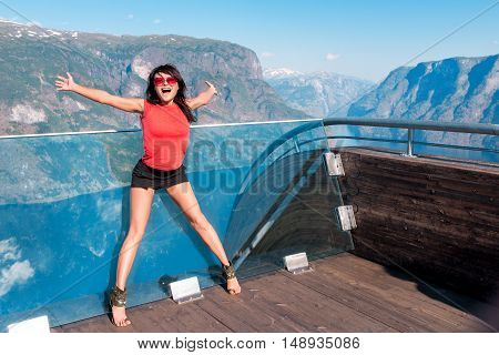 Excited emotional woman tourist at Stegastein Viewpoint with hands raised in a summer sunny day, Flam, Norway