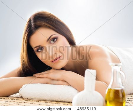 Young and beautiful girl relaxing in Christmas spa salon. Massage therapy, healing medicine and health care concept.