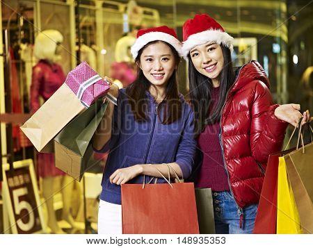 two young asian women wearing christmas carrying shopping bags