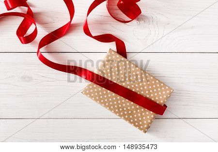 DIY hobby background. Making box for christmas or other holiday handmade present in craft paper with red ribbon. Unfinished gift on white wooden table, top view with copy space