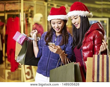 two young asian women wearing christmas hat carrying shopping bags looking at cellphone