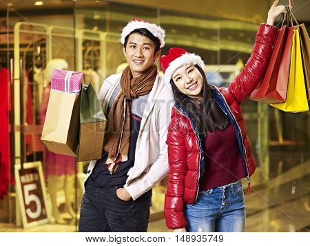 young asian couple wearing christmas hat holding shopping bags