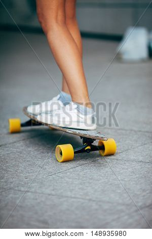girl skating on a longboard outdoors, only legs